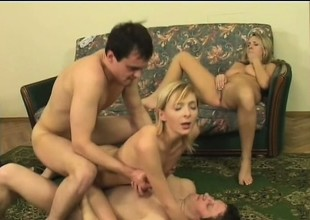 Two alluring blondes get fucked by a pair of horny studs on the couch