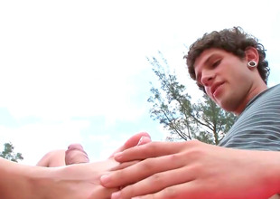 Skinny brunette AJ gives a footjob in a public
