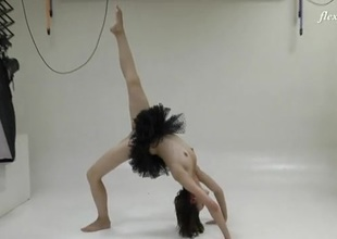 Ballerina in a black dress does standing splits