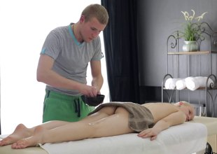 The massage therapist rubs her then puts his cock inside her