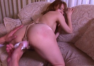 Rope keeps the dildo in her pussy as she sucks dick