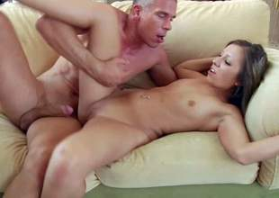 Teen brunette Sasha Hall with pierced belly button and small tits gets seduces by tall Mick Blue with strong cock and has loud orgasm while he fucks her on couch